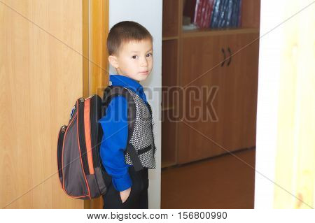 School boy go in classrom weared in school uniform and bag