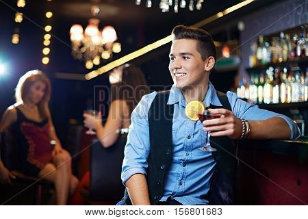 Handsome young man drinking cosmopolitan at bar