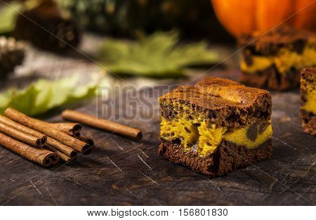 Pumpkin chocolate brownie on a dark wooden background. Baking for Thanksgiving Day. Selective focus