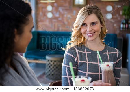 Female friends interacting with each other while having coffee in cafeteria