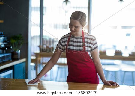 Waitress wiping table at counter in café