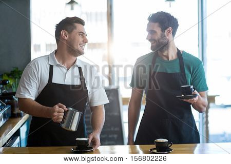 Smiling waiter interacting while making cup of coffee at counter in café