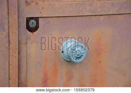 Door degraded with handle and lock in a village