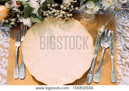 Empty plate with silverware on table, void. Restaurant serving for banquet, wedding, celebration or dinner event with flower decoration, flat lay
