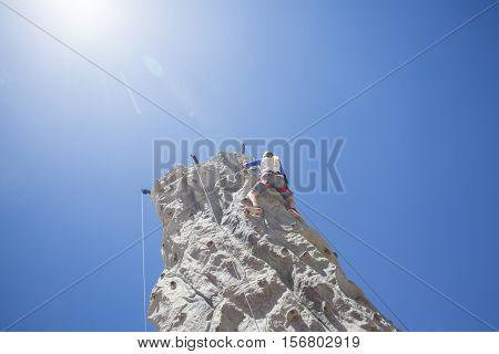 Woman ascending an outdoor Rock Climbing Wall