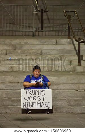 LOS ANGELES, CALIFORNIA - NOVEMBER 11, 2016: Protester texting on her cellular telephone, with her homemade sign