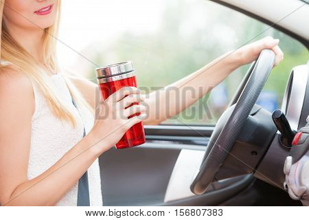 Take an energy boost. Young attractive woman sitting at the wheel drinking hot tea or coffee from vacuum flask thermos while driving the car.