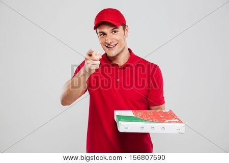 Pizza delivery man shows at camera. looking at camera. isolated gray background