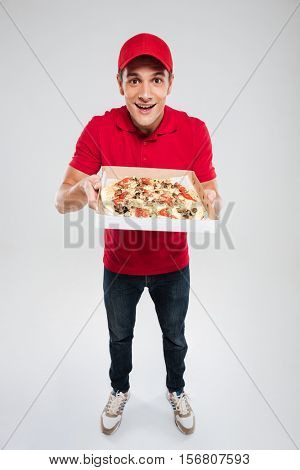 Full length of young pizza delivery man. isolated gray background
