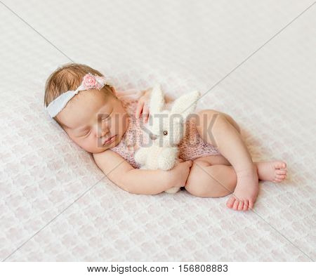 lovely sleeping newborn girl with headband and holding toy on pink blanket