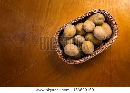 Potatoes in wicker basket on the wooden countertop