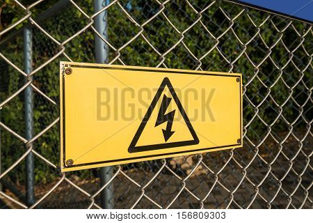 High Voltage warning sign on wires fence net
