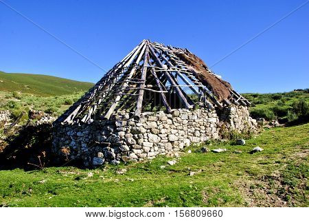 Stone house with thatched roof under construction