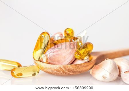 Close up garlic and oil capsule gel supplement in a wooden spoon on white background healthy vitamin supplement from garlic oil concept