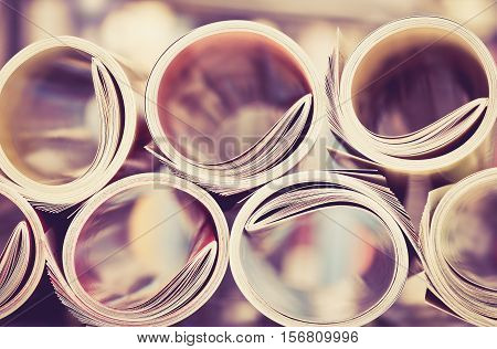 Close up edge of colorful magazine stacking roll with blurry bookshelf background for publication and publishing concept extremely shallow DOF with vintage retro color tone