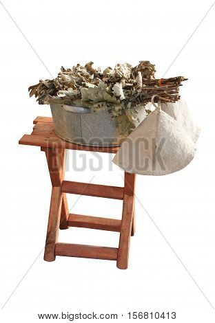 Birch brooms for a bath in the pelvis and hat on a wooden stool. Accessories for the Russian bath.