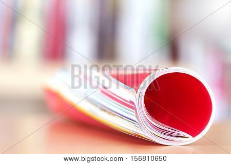 Close up edge of colorful magazine stacking roll with blurry bookshelf background for publication and publishing concept extremely shallow DOF