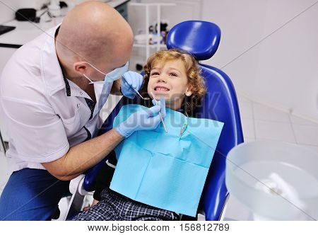 Male dentist examines the teeth of the patient cheerful child with curly red hair. Moloi boy smiling in dentist's chair