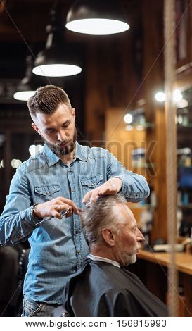 Thorough work. Side view of concentrated male hairdresser standing near his senior client and doing nice haircut.