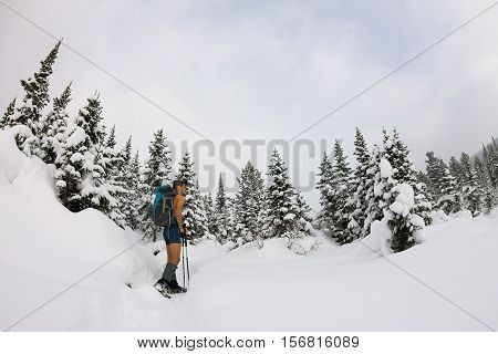 Male tourist with a backpack with a naked torso and legs is among the snowdrifts and trees.
