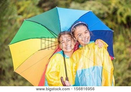 Children with colorful rainbow umbrella and raincoats standing in the rain