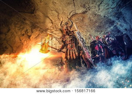 Battle Of Powerful Knights In Heavy Armor In The Dungeon. Mighty Warrior With The Flaming Axe On The