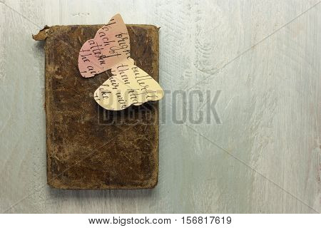 A photo of an old book with a butterfly cut out of paper toned with watercolor, shot from above on a wooden board, with copyspace