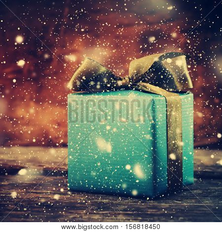 Festive Box On Wooden Christmas Background With Snowfall