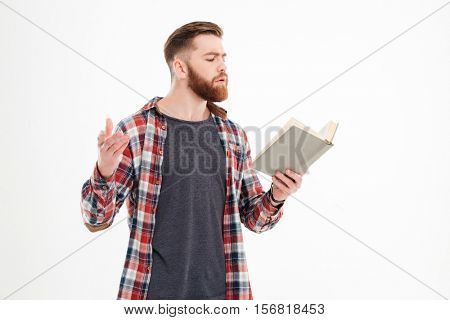 Young bearded man actor reading script over white background