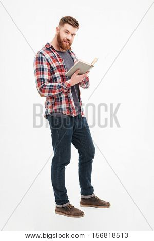 Full length portrait of a smiling bearded man in plaid shirt holding book and looking at camera over white background