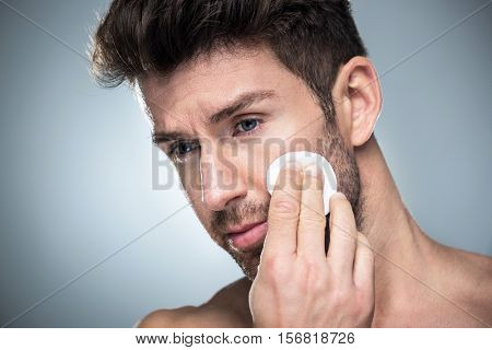 Man using cotton pad on face
