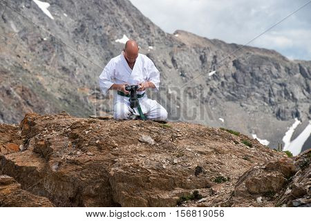 The man in a kimono sits in a lotus position on top of a mountain and watching the pictures in the camera