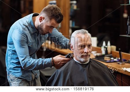 Perfect trim. Youthful attractive hairstylist standing and accurately trimming hair of old client at barbershop.