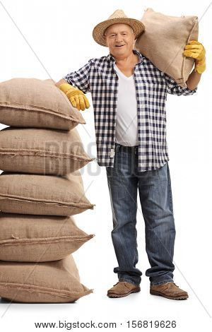 Full length portrait of a mature farmer holding a burlap sack on his shoulder and leaning on a pile of burlap sacks isolated on white background