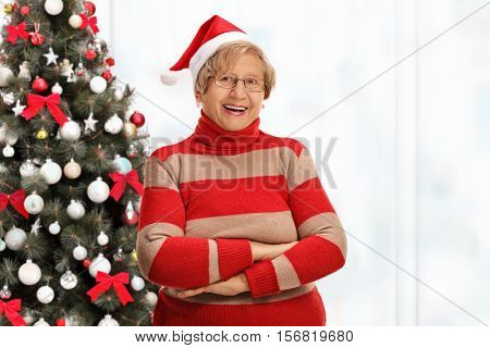 Happy elderly woman posing with her arms crossed in front of a Christmas tree