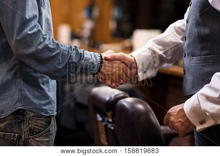 Good bargain. Close up portrait, two man different status standing and shaking hands of each other