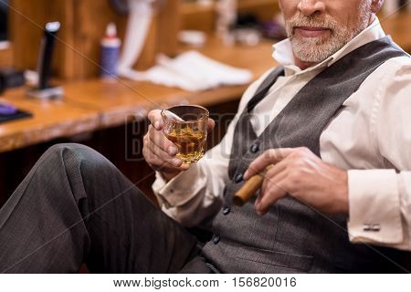 Showing off. Close up of senior bearded man wearing luxury suit sitting on armchair with whiskey glass and cigar.