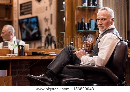 Its my business. Handsome bearded senior man sitting on leather armchair with whiskey glass and cigar in front of mirror at barbershop.