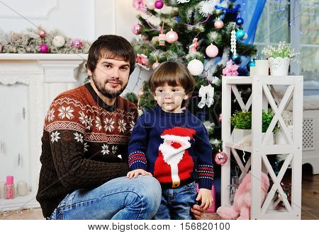 father and son in a warm sweater sitting on the background of the Christmas tree in the studio