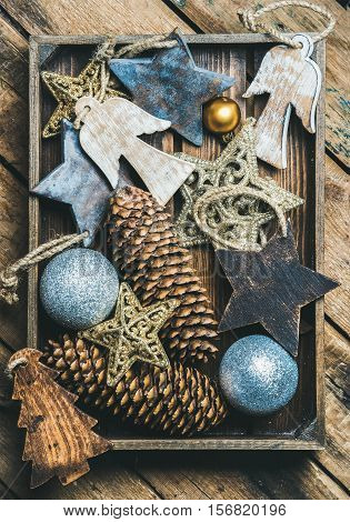 Christmas tree glittering toy stars, balls, pine cones and angel shaped wooden toys in wooden box over rustic background, top view, vertical composition