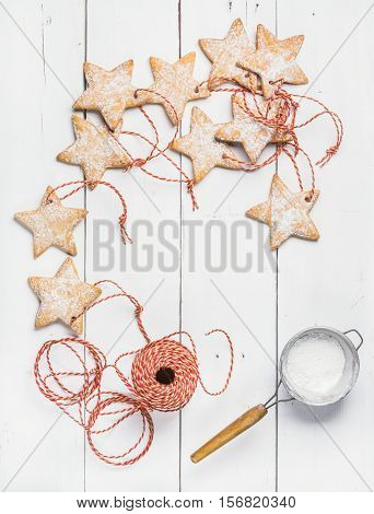 Christmas homemade gingerbread star shaped cookies with sugar powder in sieve and red decoration rope over white wooden background, top view, copy space, vertical composition