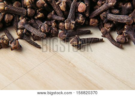 Clove spice closeup on wooden beige background. Decorative border of buds clove spice on wood board.
