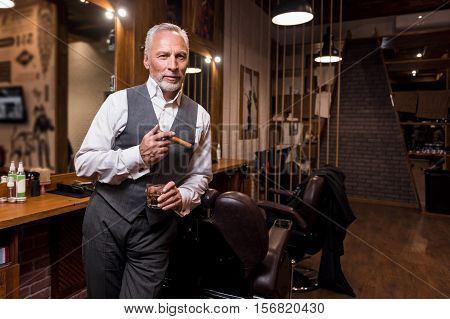 Sign of status. Portrait of handsome bearded senior businessman standing and holding whiskey glass with cigar at barbershop.