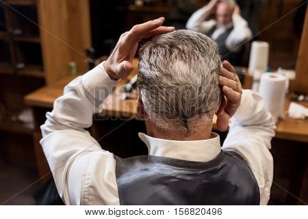 Beautify yourself. Close up back view of senior gentle man styling his grey hair himself at barbershop.
