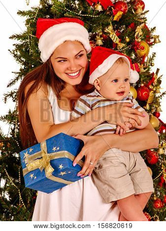 Mom wearing Santa hat holding baby with gift box under Christmas tree. Happy childhood.