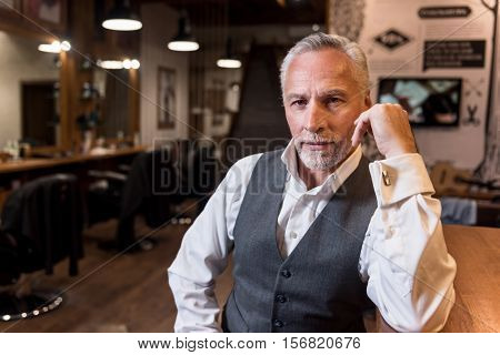 Intent glance. Portrait of attractive senior businessman wearing luxury suit sitting at bar counter, leaning on arm and looking forward.