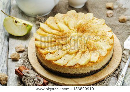 Cinnamon apple caramel cheesecake on wood background