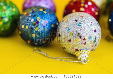 multicolor christmas ball on yellow background texture