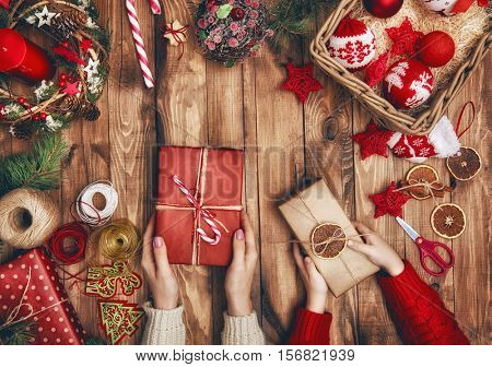 Merry Christmas and Happy Holidays! A mother and daughter prepare Xmas gifts. Baubles, presents, candy with christmas ornaments. Top view. Christmas family traditions.