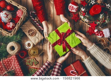 Merry Christmas and Happy Holidays! A mother, father and their daughter prepare Xmas gifts. Baubles, presents, candy with christmas ornaments. Top view. Christmas family traditions.